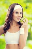 Young happy smiling woman in sportswear with green apple, outdoo — Stock Photo