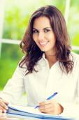 Portrait of young happy brunette businesswoman at office — Stock Photo