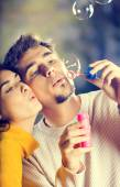 Young attractive happy couple blowing bubbles outdoors — Stock Photo