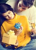 Young happy couple with gifts and champagne outdoors — Stock Photo