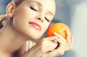 Young woman with orange at home — Stock Photo
