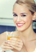 Portrait of woman with orange juice, indoors — Stock Photo