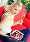 Woman with sweets and champagne at home — Stock Photo