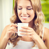Young woman drinking coffee or tea, at home — Stock Photo