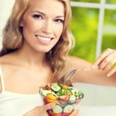 Woman eating salad, indoors — Stock Photo