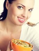 Woman eating muesli or cornflakes — Stock Photo