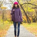 Young beautiful woman walking along autumn city park — Stock Photo #54983699