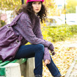 Young beautiful woman sitting on a bench in a city park — Stock Photo #54983701