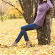 Young beautiful woman resting in autumn city park — Stock Photo #54983719