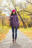 Young beautiful woman walking along autumn city park — Stock Photo
