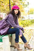 Young beautiful woman sitting on a bench in a city park — Stockfoto