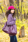 Young stylish woman with a big bag in the autumn park — Stock Photo