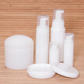 Open jar of cream and other body care cosmetics — Stock Photo