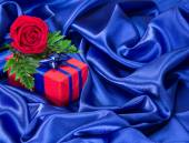 Gift with rose on silk fabric — Stock Photo