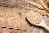 Wheat bran in wooden spoon with wheat ears — Stock Photo