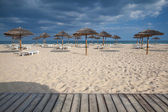 Different parasols and sun loungers on the empty beach on Tavira — Stock Photo