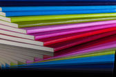 Twelve different colors diaries on a glass desk — Stock Photo