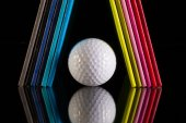 Twelve different colors diaries and golf ball on a glass desk — Stock Photo