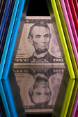 Twelve different colors diaries and US dollar banknote on a glas — Stock Photo