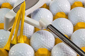 White golf balls in the yellow box and golf putter — Stock Photo