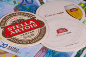 Beermats from Stella Artois and eur banknotes. — Stock Photo