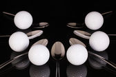 Teaspoons and golf equipments on the black glass table — Stock Photo