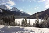 A frozen lake in front of a mountain in the rockies under blue s — Stock Photo