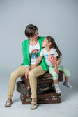 Mother and daughter sitting on suitcases — Stock Photo