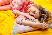 Girl sleeping on the yellow sheet — Stock Photo