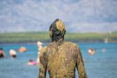 Unrecognizable person in healthy mud on beach — Stock Photo