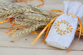 Sachet with ukrainian embroidery, wheat and oat on wooden background — Stock Photo