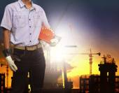 Engineer man working with white safety helmet against crane and  building construction site use for civil engineering and construction industrial business — Stock Photo