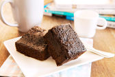 Browny cake ready to eat on white dish with coffee cup and magaz — Stock Photo
