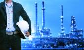 Engineering man and safety helmet standing against oil refinery — Stock Photo