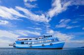 Passenger wooden boat floating on blue sea water with beautiful — Stock Photo