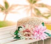 Beautiful straw hat decorated with artifucial flowers on wood ta — Stock Photo