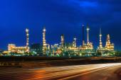 Oil refinery plant against beautiful blue dusky sky and vehicle  — Stock Photo