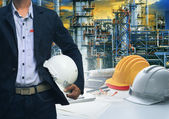 Engineering man standing with white safety helmet against  oil r — Stock Photo