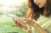 Beautiful woman playing and touching on smart phone screen in ou — Stock Photo