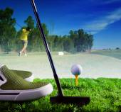 Golf ball and putter on green grass of course against young man  — Stockfoto