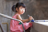 Lovely kid practice for writing on white broad before class lear — Stock Photo