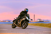 Young man riding sport touring motorcycle on asphalt highways ag — Stock Photo