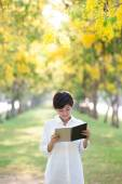 Portrait of young beautiful asian woman standing in yellow flowe — Stockfoto