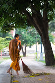 Thai monk daily cleaning temple area — Stock Photo