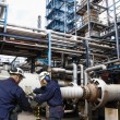 Oil workers inside industrial oil refinery — Stock Photo #53803113