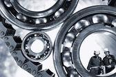Mechanics standing inside giant ball-bearings — Stock Photo