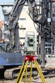 Surveying instrument and heavy construction machinery — Stock Photo