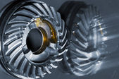 Titanium cogwheel mirrored in titanium background — Stock Photo