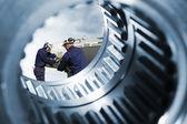 Engineers, workers seen through giant cogwheels — Foto de Stock