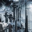 Oil and gas workers and large smokey refinery — Stock Photo #74383109